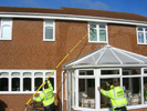 Cleaning windows above conservatories with the reach and wash system.